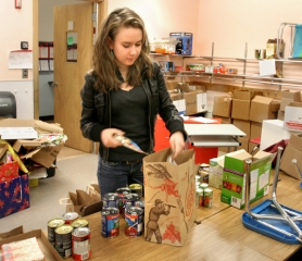 by: Jim Clark Caitlin Morrison loads up a bag of food that will go to a child at Oliver Elementary School.