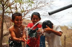 children playing and washing with water from pipe